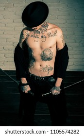 Honor and dignity. Harakiri, suicide ritual. Samurai, buddhist concept. Man with sword standing on wooden floor, top view. Warrior in black hat and open clothes showing tattooed torso.