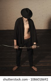 Honor and dignity. Man with sword standing on wooden floor barefoot, top view. Samurai, buddhist concept. Warrior in black hat and open clothes showing tattooed torso. Harakiri, suicide ritual.