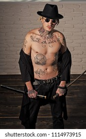 Honor and dignity. Warrior in black hat and open clothes showing tattooed torso. Samurai, buddhist concept. Harakiri, suicide ritual. Man with sword standing on wooden floor, top view.
