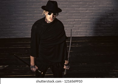 Honor and dignity. Warrior in black sunglasses, hat and clothes, top view. Samurai, buddhist concept. Man with swords standing on wooden floor. Harakiri, suicide ritual.
