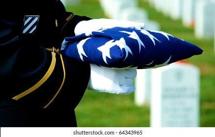 Honor Guard holding folded American flag at grave site at Arlington National Cemetery