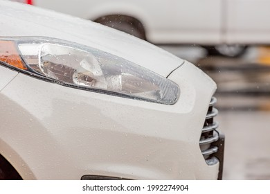 Hood, bumper, and lights on a wet white car driving in the rain