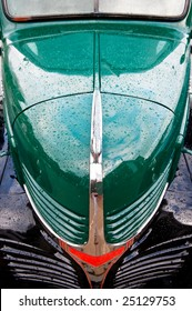 Hood of a green and black antique truck with raindrops