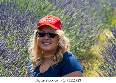Hood River, OR - July 8, 2019: Blonde, sexy Republican woman Donald Trump supporter wears a MAGA Hat with thug life sunglasses while sitting in lavender field