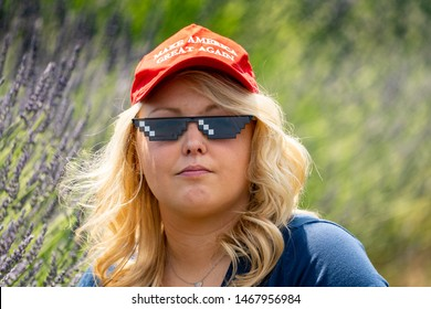 Hood River, Oregon - July 8, 2019: Blonde, sexy but serious Republican woman Donald Trump supporter wears a MAGA Hat with thug life sunglasses while sitting in a lavender field