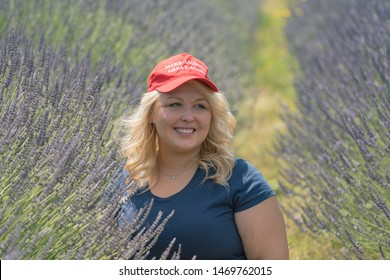 Hood River, Oregon - July 8, 2019: Blonde, sexy Republican woman Donald Trump supporter wears a MAGA Hat with thug life sunglasses while sitting in a lavender field