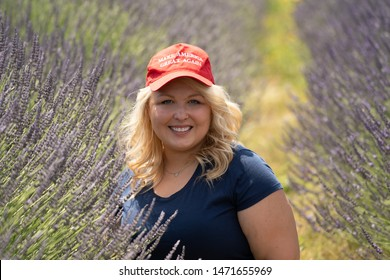 Hood River, Oregon - July 8, 2019: Blonde, sexy Republican woman Donald Trump supporter wears a MAGA Hat while sitting in a lavender field
