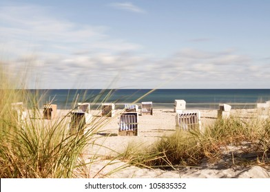 hooded beach chairs at the baltic sea, focus on the dune grass in foreground