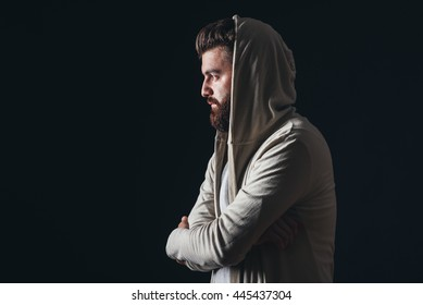 hooded and bearded man in studio, isolated black