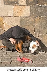 Hooded beggar with two Dogs on the Streets of Prague