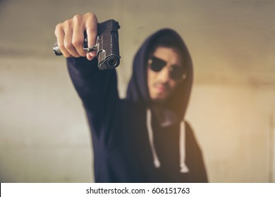 Hooded criminal gesturing gun shooting.,spooky gangster person pointing gun at viewer.,Stealing the theft in a black Jacket Hood,not known in the middle of the night crime,gangster concept,