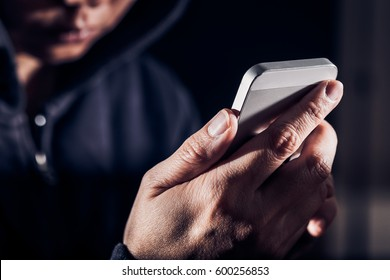 Hooded cyber crime hacker using mobile phone internet hacking in to cyberspace,online personal data security concept