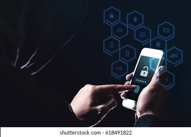Hooded cyber crime hacker using mobile phone with icon diagram features hacking in to cyberspace stealing online personal data, Security on internet concept