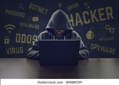 Hooded cyber criminal stealing secrets with laptop
