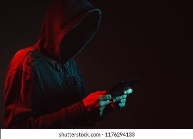 Hooded faceless hacker with tablet computer in cybersecurity concept