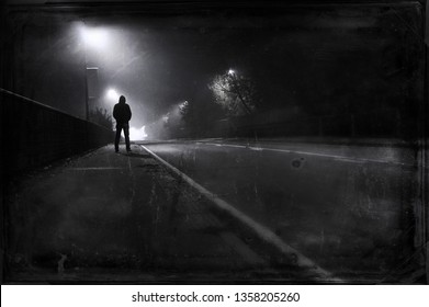 A hooded figure looking down a street on a foggy winters night. With a grainy vintage, muted edit.