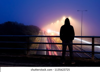 A hooded figure at night looking down on a busy motorway with traffic trails. Using a saturated, heavily contrasted urban edit.