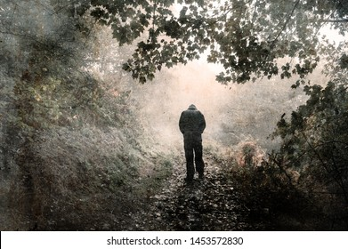 A hooded figure walking away from the camera on a misty woodland path with shoulders hunched and looking down. With a grunge, vintage edit