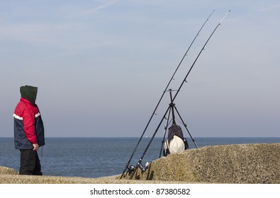 Hooded fisherman on a stone jetty watching his rods