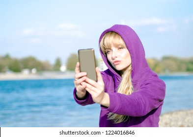 Hooded girl taking selfie photo on cell phone using fun application.Sending kiss on mobile phone.Sitting by the river and holding mobile phone