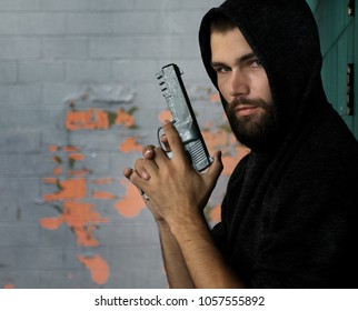 Hooded gunman with beard holding a sig sauer pistol ready to fire in a grungy alley