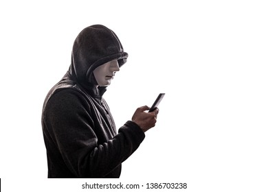 Hooded hacker with mask holding smartphone isolated on white background