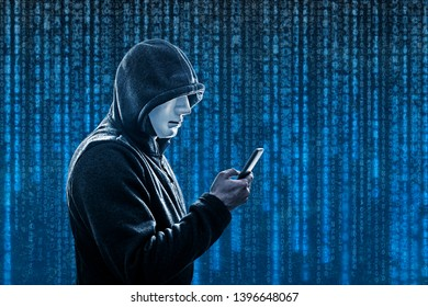 Hooded hacker with mask holding smartphone