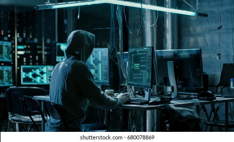 Hooded Hacker Using His Comuter with Different Information to Break into Corporate Data Servers and Infects them with Virus. His Hideout Place has Dark Atmosphere, Multiple Displays, Cables Everywhere