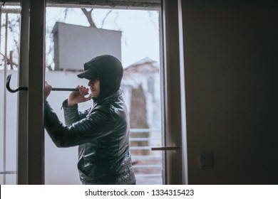 Hooded housebreaker forcing window lock to make a theft in a house