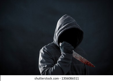 Hooded man with bloody knife in the dark