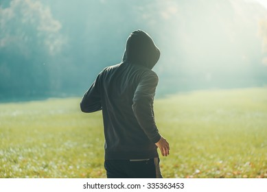 Hooded man jogging in the park in early autumn morning, sport, recreation and healthy lifestyle concept, retro toned image with selective focus