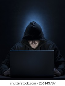 Hooded man on the computer, for hacking,spying,internet security themes