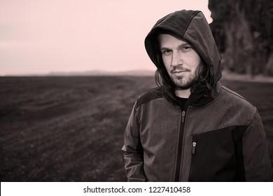 Hooded man portrait in barren landscapes of iceland