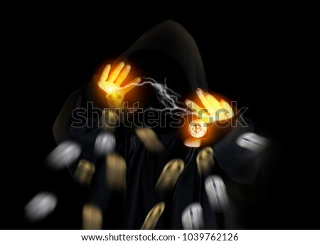 Hooded man in shadow with crypto currency bitcoin flying on black background.