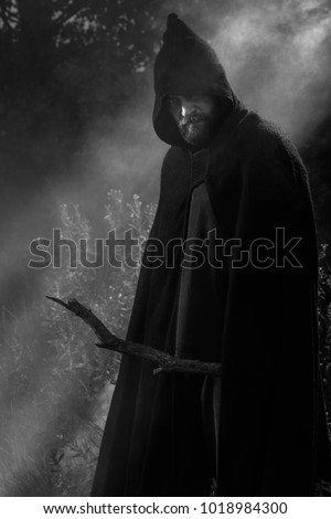 hooded man wearing cloak mysterious fantasy stock photo