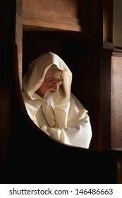 Hooded monk sitting in a choir seat of a medieval church
