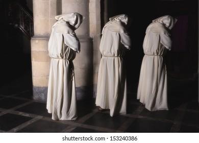 Hooded monks walking in a dark medieval church