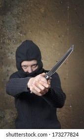 Hooded person with Ninja Knife on grunge background. Selective focus on knife.