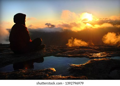 A hooded person on the top of the hill looking at the sunset. Norway. Kjerag mountain. Lysefjord.