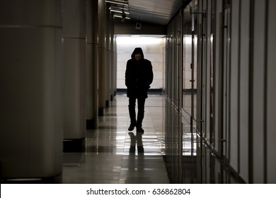 Hooded sad man wearing black walking along dark empty hallway, looking down, lonely introvert hiding from the world, frustrated homeless guy having deep depression, wandering solitary outcast
