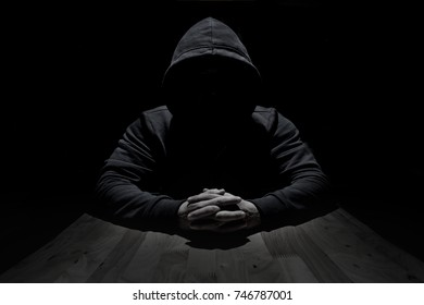 Hooded silhouette on black background,hands intertwined fingers on the table