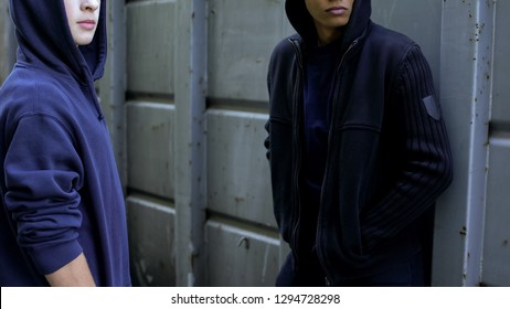 Hooded teenagers waiting for victim, extortion of money, young criminals