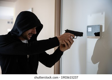 The hooded thief with a gun breaks into the apartment.