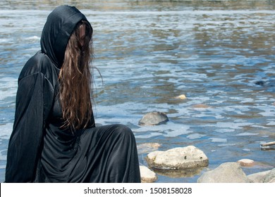 Hooded Woman with dark long hair in black robes in front of the Lake. Witches. Halloween and Gothic. Witchcraft and magic. Back to Nature concept.