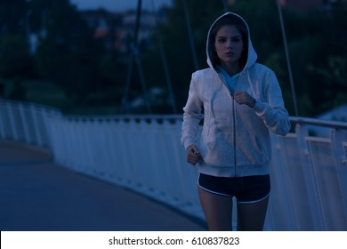Hooded young woman running by night in the park. Fitness and workout wellness concept. Sports outdoors. Cityscape Background