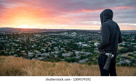 Hoodie man photographer and traveler watching sunrise over Auckland city at Mount Eden view point in Auckland, North Island, New Zealand. Travel Oceania. Success or achievement concepts