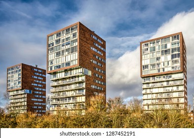 """Hoogvliet, The Netherlands, January 14, 2019: three brick residential towers with """"cyclops eyes"""" looking out over the river Oude Maas"""