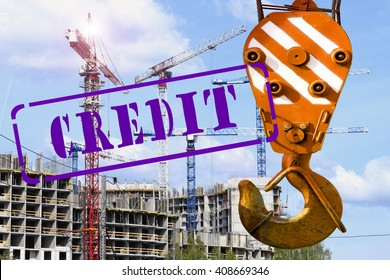 """The hook of the crane and the stamp """"credit"""" against the construction"""