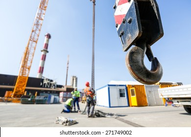 Hook of a mobile lifting crane on a construction site, capable of lifting 25 tons of load with workers in the background. Heavy duty machinery for heavy construction industry.