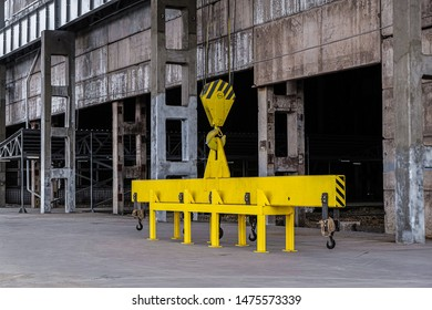 Hook of overhead traveling crane with yellow linear traverse. Industrial area.